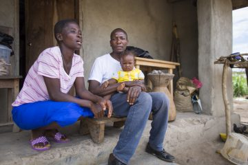 Harrison Sakela, the first Ebola survivor in Liberia, sits outside his home with his wife and young daughter.