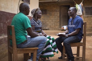 Darlington Jallah, a health coordinator for Samaritan's Purse, sits with Jenneh Gbembo, an Ebola survivor, at her home in Lofa County. Darlington encourages Jenneh with verses from the Bible.
