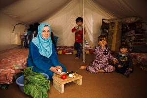 Ala's wife prepares food as the children play behind her. The family received food aid from Samaritan's Purse and World Food Programme.