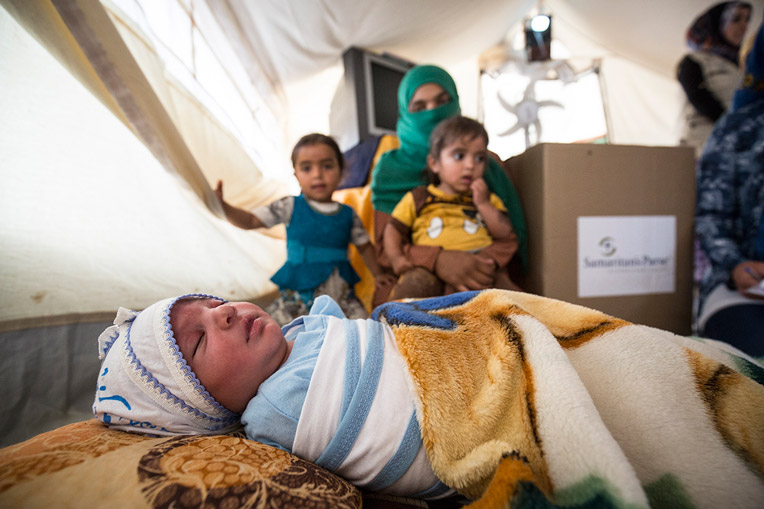 FATIMA (GREEN SCARF) AND HER CHILDREN RECEIVE AN INFANT CARE BOX FROM SAMARITAN'S PURSE.