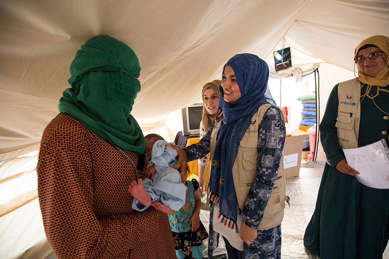 Health workers encourage Fatima in her journey as a mother.