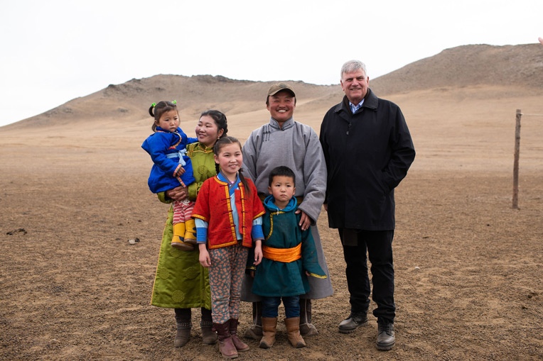 Franklin Graham stands with Ulzii's family in the grasslands of Mongolia's Tuv Province. Ulzii (far left) is held by her mother Myadagaa and father Adiyaa, as her sister Tumee and brother Tulgaa stand by.