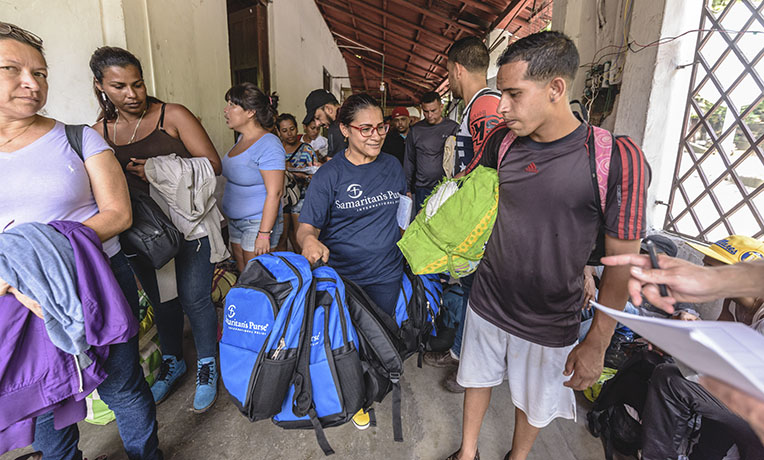 Viviana Paez distributes backpacks to Venezuelans migrants in La Don Juana, Colombia.