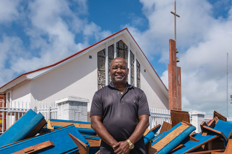 Pastor Keith Russell stands in front of First Baptist Church roughly six months after Hurricane Dorian damaged their pews.
