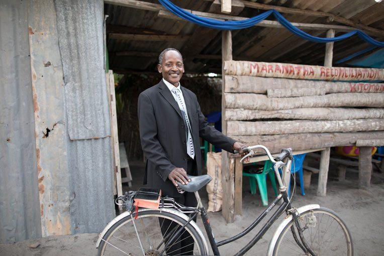 PASTOR MARCO KAYUMBO RIDES HIS BIKE TWICE WEEKLY TO PREACH AT HIS CHURCH PLANT, MARANATHA CHURCH KITOMONDO.