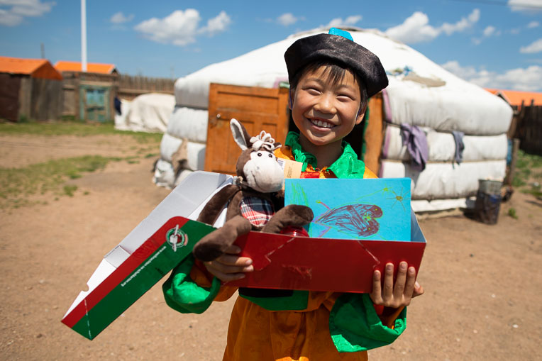 "A BOY IN MONGOLIA SMILES AFTER RECEIVING HIS ""WOW"" TOY AND A PERSONAL NOTE IN THE SHOEBOX GIFT LOVINGLY PACKED JUST FOR HIM."