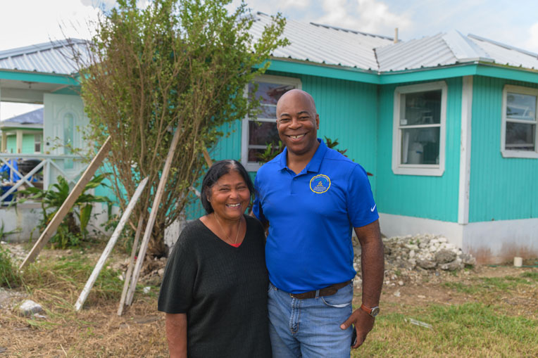 Samday Dames thanks Pastor Peter Watson for the new metal roof on her home through the partnership with Samaritan's Purse.