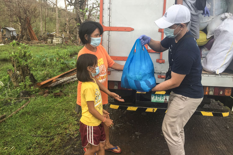 A family in the Philippines receives relief items from our staff.