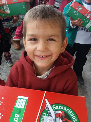 Young boy smiling with shoebox