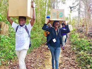 University students transport shoeboxes through the jungle