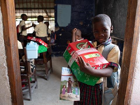 Boy in classroom doorway holding a shoebox gift