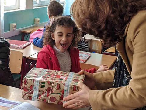 girl open mouthed at shoebox gift