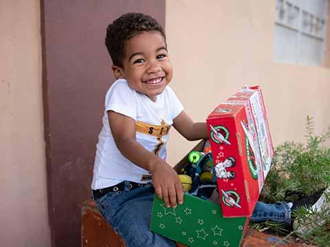 boy with shoebox gift smiles